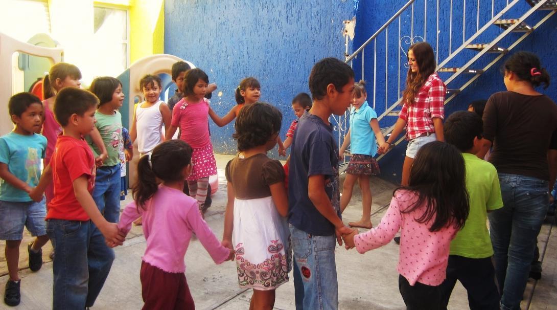 Een groep Projects Abroad vrijwilligers werkt met kinderen in Mexico en speelt samen een spel in een dagzorgcentrum.